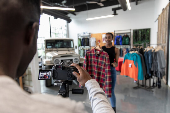 Sporting goods shop owners filming clothing product review in store