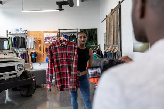 Sporting goods owners filming clothing product review in shop