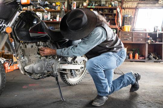 Senior male cowboy fixing motorcycle in barn workshop