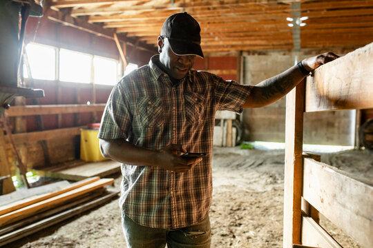 Male farmer using smart phone in barn