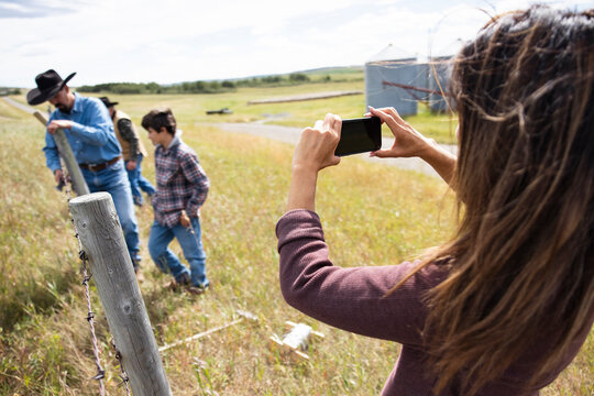 Female rancher with camera phone photographing family fixing fence