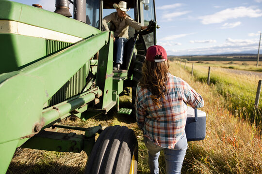 Female farmer bringing lunch to husband in tractor in sunny field