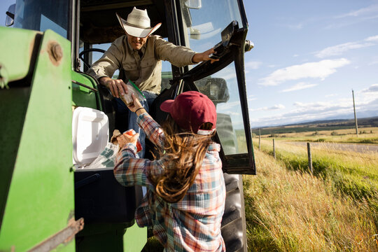 Female rancher bringing lunch to husband in tractor in sunny field