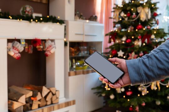 A male hand holds a smartphone. The man is standing in a Christmassy decorated living room. Christmas tree and fireplace console.