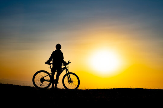 The moment of the cyclist enjoying nature watching the sunrise