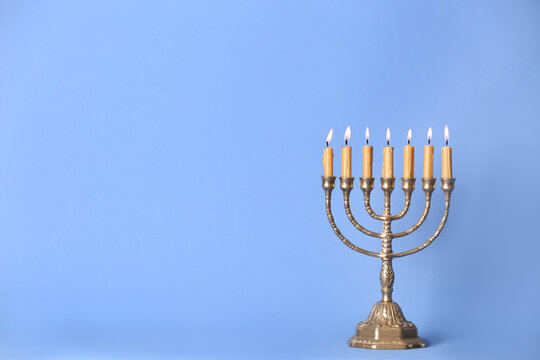 Golden menorah with burning candles on light blue background, space for text