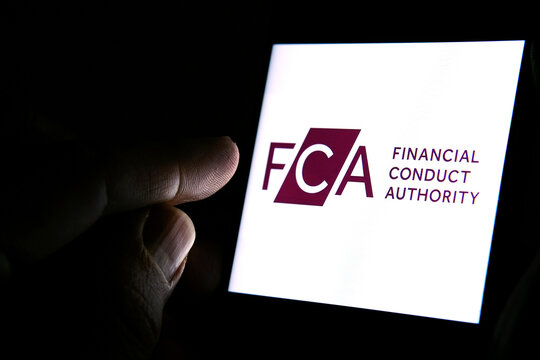 FCA Financial Conduct Authority logo on the smartphone and finger pointing at it in the dark room. Concept.  FCA is a financial regulatory body in the United Kingdom.