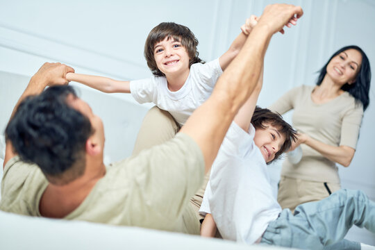Playing with father. Portrait of cheerful little latin boy having fun, playing with his parents and sibling, lying together on a bed at home