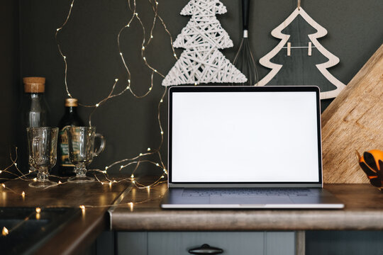 Laptop computer with white blank screen mock up, on the kitchen table with Christmas decoration.