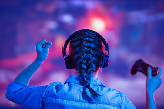 View from back of gamer woman with pigtail playing video game at home in front of big screen with headphone and raised hand up. Colorful neon led lights background. Streamer concept. Macro shot.