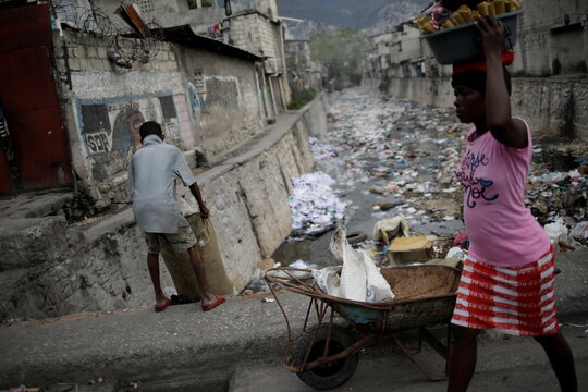 A woman carrying a bucket on her head walks next to a man throwing garbage to a canal, in Port-au-Prince
