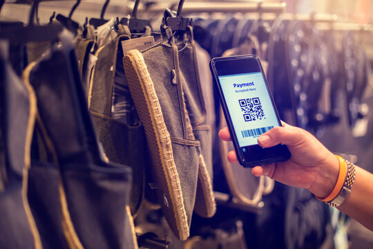 Selective focus to payment QR code tag on smartphone with blurry many cloth shoes in the store to accepted generate digital pay without money. Qr code payment concept.