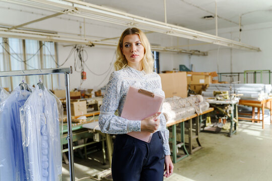 Female entrepreneur manager at factory holding clipboard looking to the side serious worried about the crisis due to economy recession - small business problems concept copy space