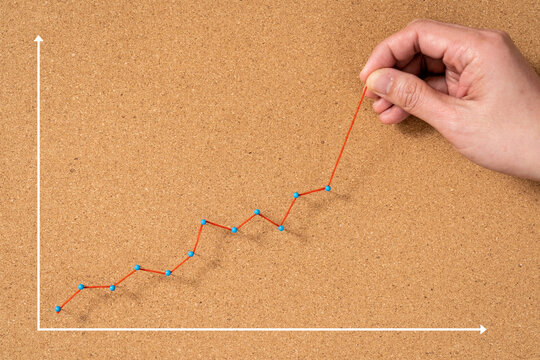Hand pulling up red growing line in chart as sign of business growth
