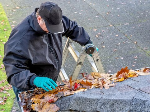 Man cleaning leaves from roof gutter