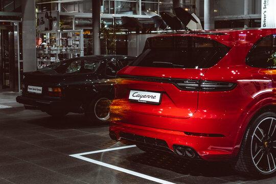 Porsche car dealer luxury showroom global company cayenne night glow