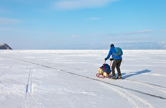 A tourist travels on the snow-covered frozen Lake Baikal on skates and with a tent on a sleigh. Extreme tourism during the cold season. Active winter holidays