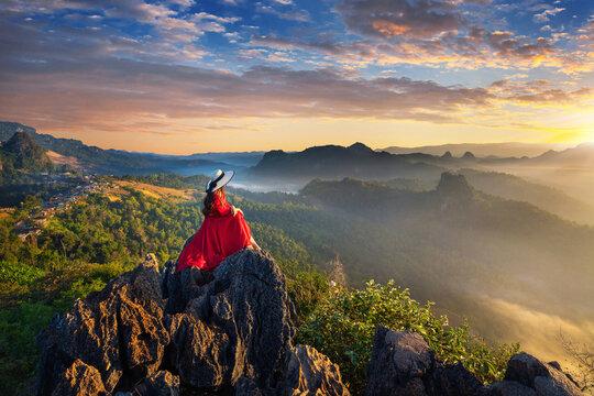 Beautiful girl sitting on sunrise viewpoint at Ja Bo village, Mae hong son province, Thailand.