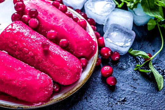 frozen cowberry and fruit ice-cream on dark table background