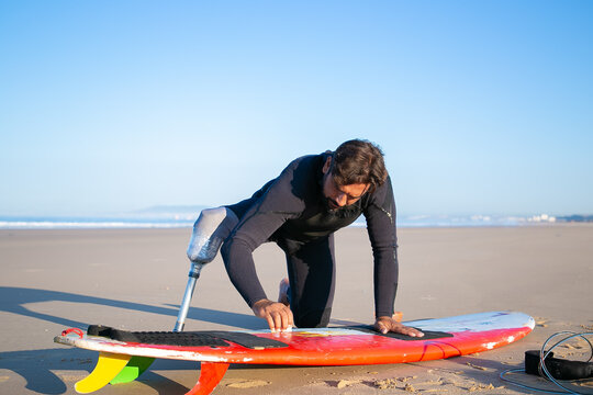 Sporty man in wetsuit wearing artificial limb, waxing surfboard on sand on ocean beach. Artificial limb and active lifestyle concept