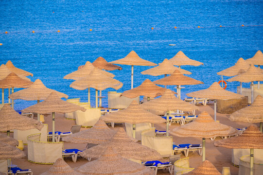 Relaxing at paradise beach - Chaise lounge and parasols - travel destination Hurghada, Egypt