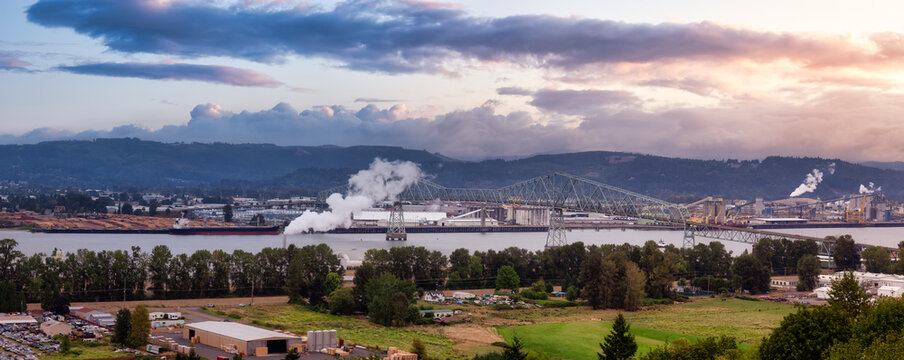 Longview, Washington, United States of America. Aerial Panoramic View of Port, Industrial Sites and Lewis and Clark Bridge over Columbia River. Sunrise Sky