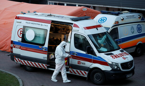 A paramedic walks near an ambulance amid the coronavirus disease (COVID-19) outbreak, in front of a hospital in Warsaw