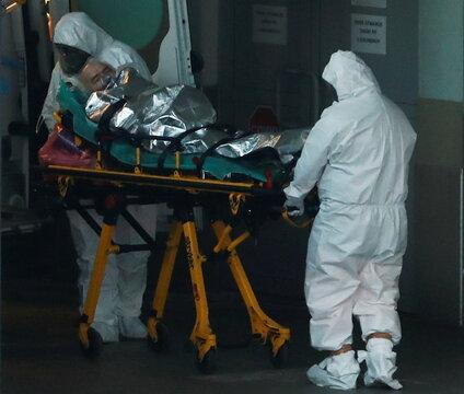 Paramedics transport a COVID-19 patient at a hospital in Warsaw