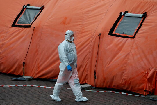 A paramedic walks amid the coronavirus disease (COVID-19) outbreak, in front of a hospital in Warsaw