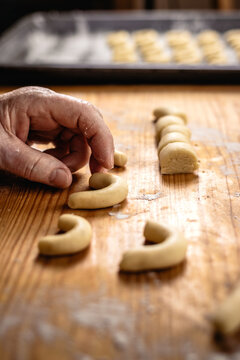 Making homemade traditional christmas cookies. Baking vanilla crescent rolls knows as vanillekipferl. Senior woman cooking sweet food from pastry dough