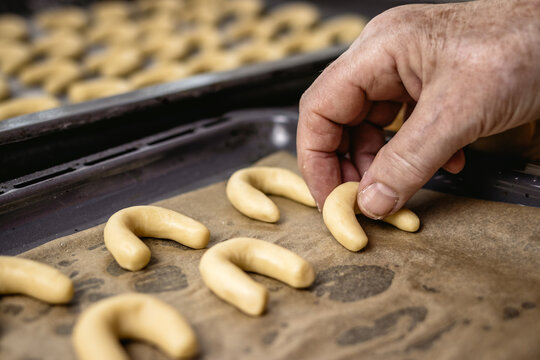 Senior woman is putting vanilla crescent rolls knows as vanillekipferl on baking tray. Homemade christmas sweets ready for baking