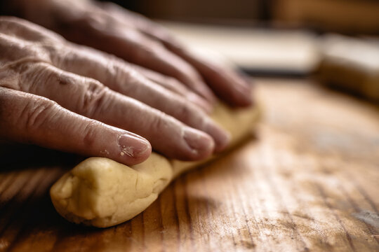 Senior woman is rolling pastry dough by hand