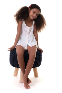 Cute multiracial small girl sitting on a stool seat