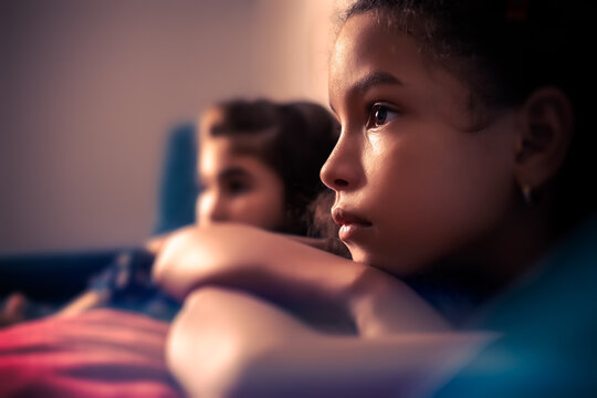 Portrait of two small girls watching TV