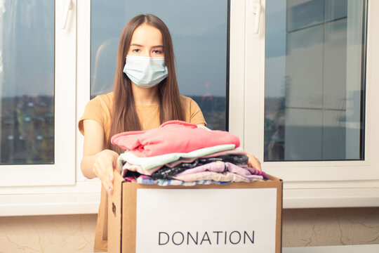 Charity and assistance to the poor, homeless, and needy. A masked volunteer girl puts clothes in a donation box