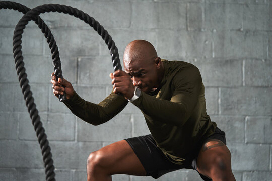 Black man training with battle ropes in crossfit