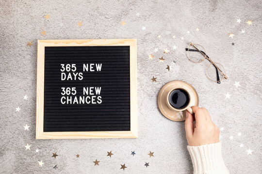 365 new days, 365 new chances. Letter board with motivational quote on grey concrete background with hand holding coffee cup, golden stars and glasses. New year's resolutions and goal setting concept