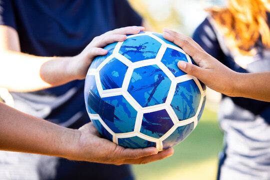 Soccer team hands huddled on ball