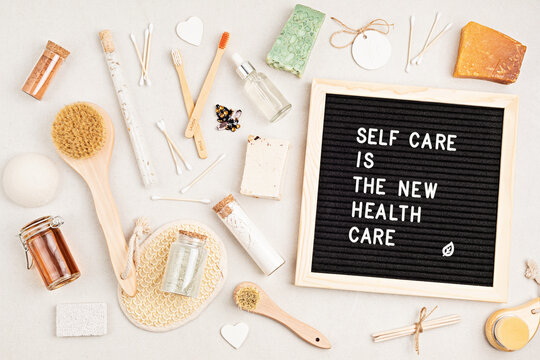 Self care is the new health care. Motivational quote on black letter board with variety of organic body and face care products. Natural homemade eco friendly beauty products