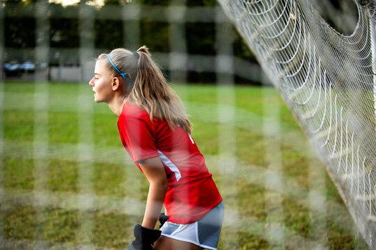 Teenage girl playing goalie on soccer field