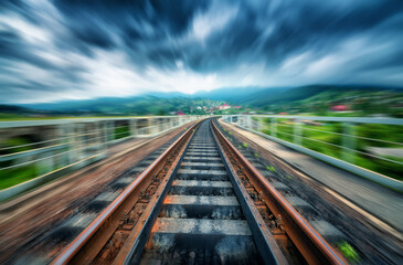 Railroad bridge in mountains in overcast day with motion blur effect. Railway station and blurred background at moody sunset. Industrial landscape with railway platform in speed motion. Concept Fotobehang
