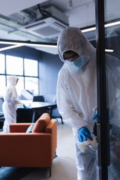 Health workers in protective clothing disinfecting creative office