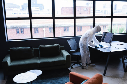 Health worker in protective clothing disinfecting creative office