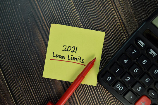 2021 Loan Limits write on sticky notes isolated on Wooden Table. Finance concepts