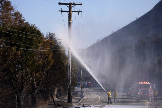 Firefighters put out a fire on a power pole during the wind driven Bond Fire wildfire near Lake Irvine in Orange County, California