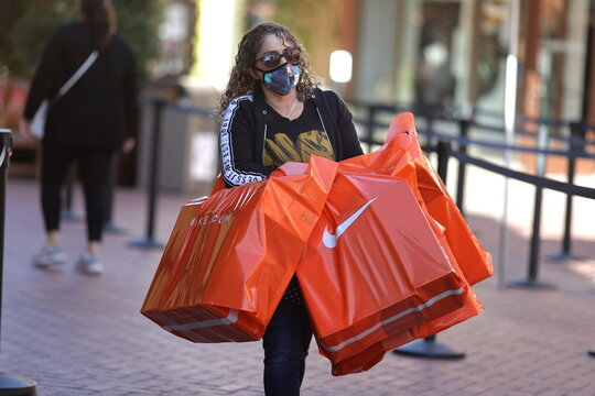 A woman carries Nike shopping bags at the Citadel Outlet mall, as the global outbreak of the coronavirus disease (COVID-19) continues, in Commerce