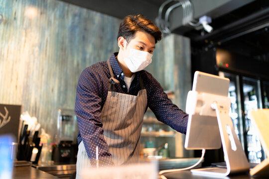 Asian barista man wearing mask working on digital menu in laptop.