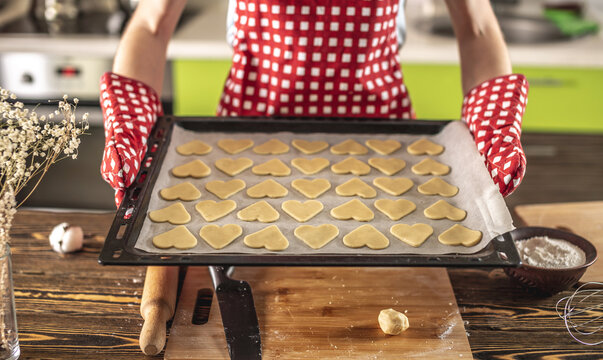 Raw homemade cookies in the shape of heart on a baking sheet for baking. Concept of fresh homemade cakes or a surprise for Valentine's day