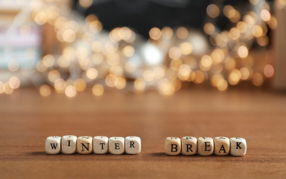 Cubes with phrase Winter Holidays and blurred Christmas decor on background. Space for text