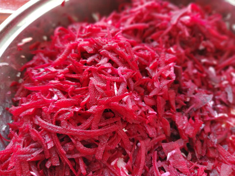 grated burgundy juicy beets in a saucepan close-up. Finely chopped beets for salads, soups, borscht. A vegetarian anti-cancer diet. Raw food diet. Soft focus. Shallow depth of field